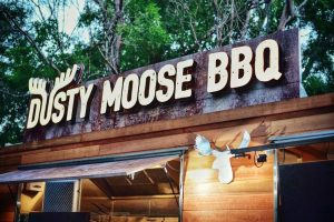 A close-up of the illuminated sign on the Dusty Moose food trailer.