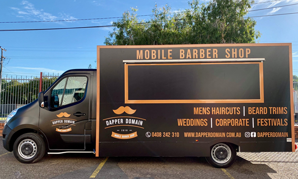 Side view of the Dapper Domain mobile barber shop truck.